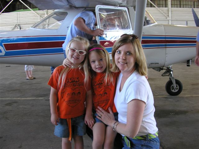 A woman and 2 pre-school girls pose in front of a small airplane in the hangar.