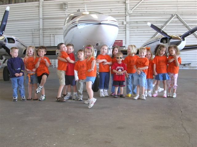 The students of the Methodist Pre-School pose for a class picture in front of an airplane.